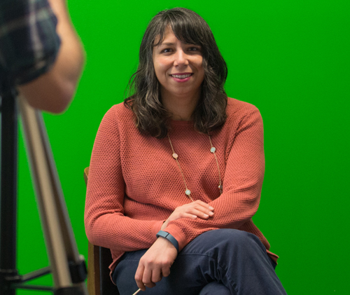 Amy Vecchione sits in front of the green screen in the Albertsons Library MakerLab.