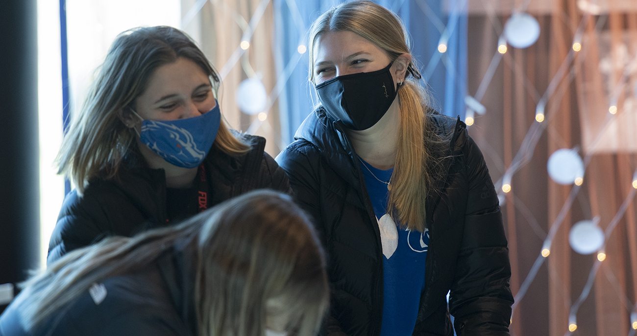 Students wearing masks laugh together