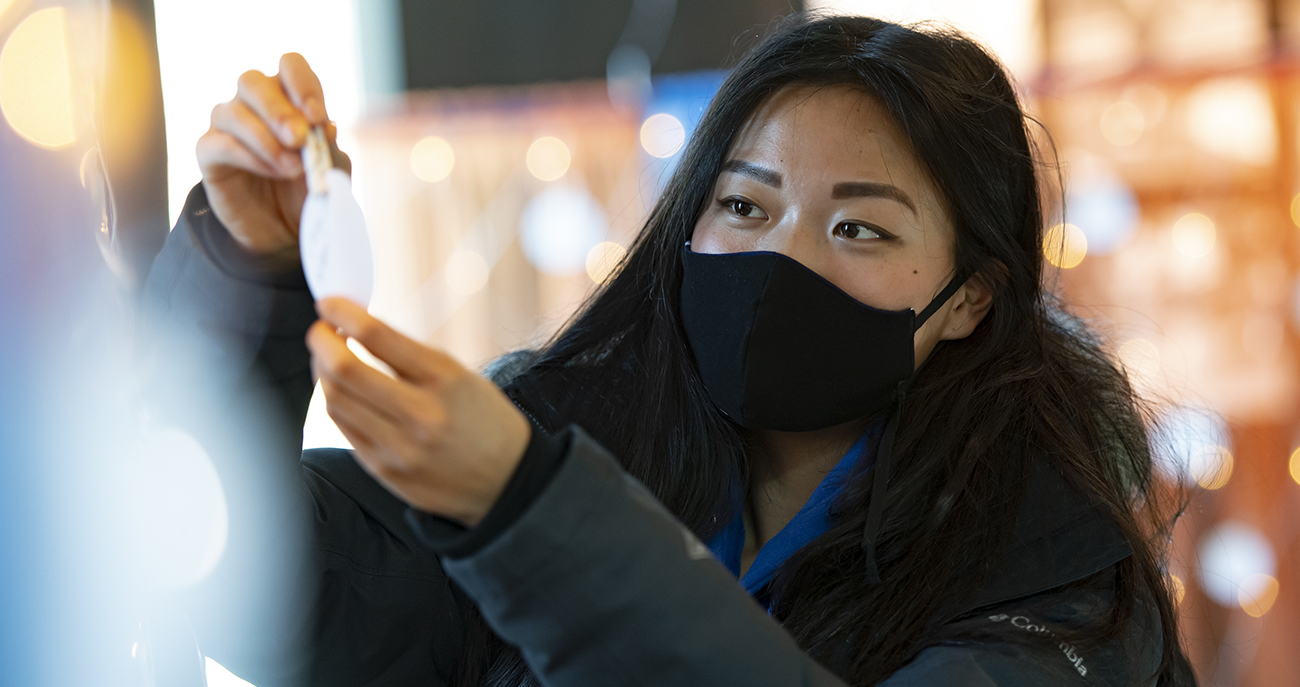 Student wearing mask adds note of hope to wall