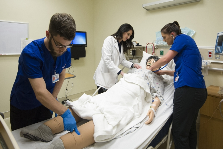 School of Nursing, Simulation Center, Classroom, Allison Corona photo. Students working with Simulation Center Manikin