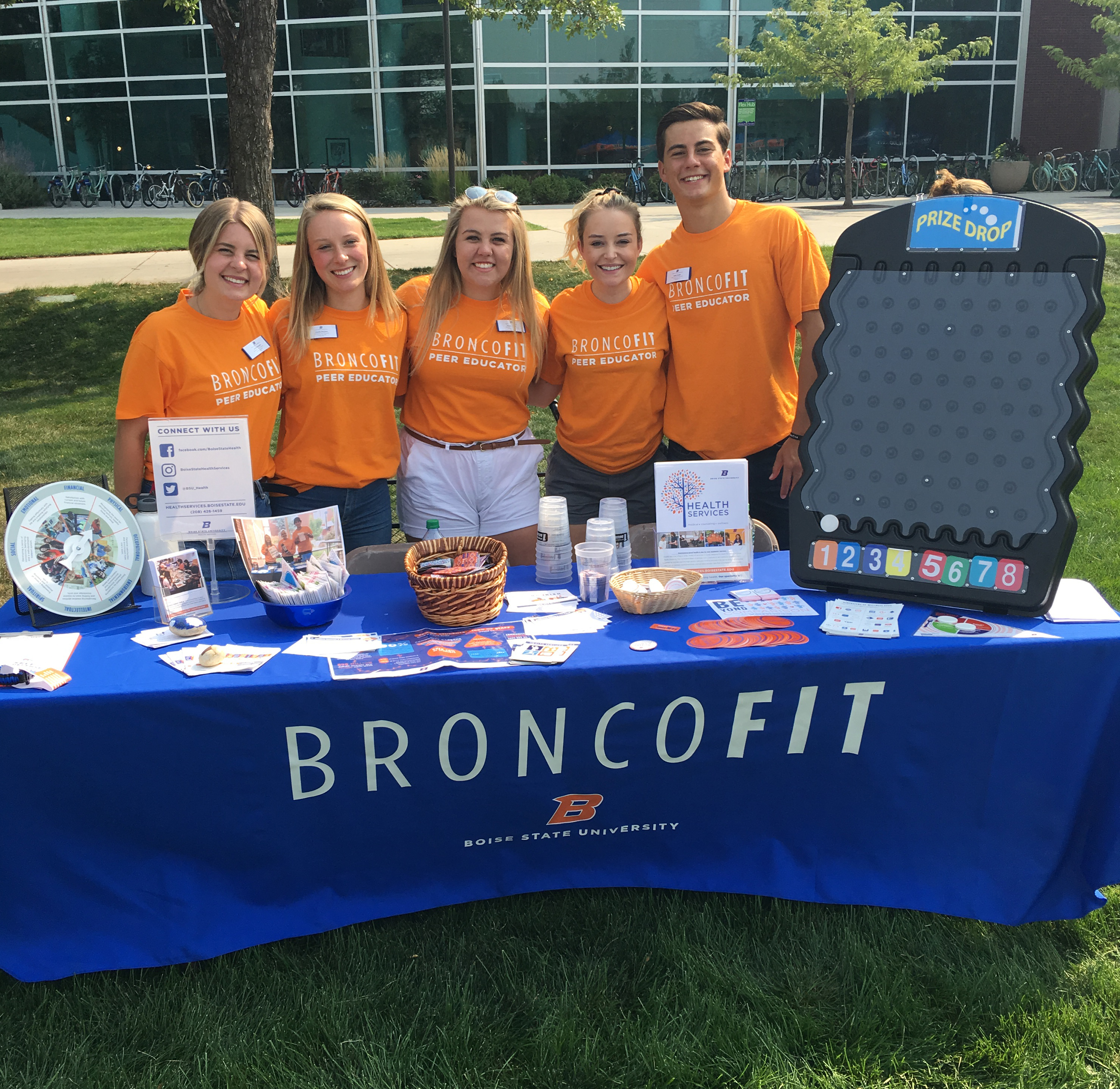 Peer Educators standing infront of table that reads BroncoFit