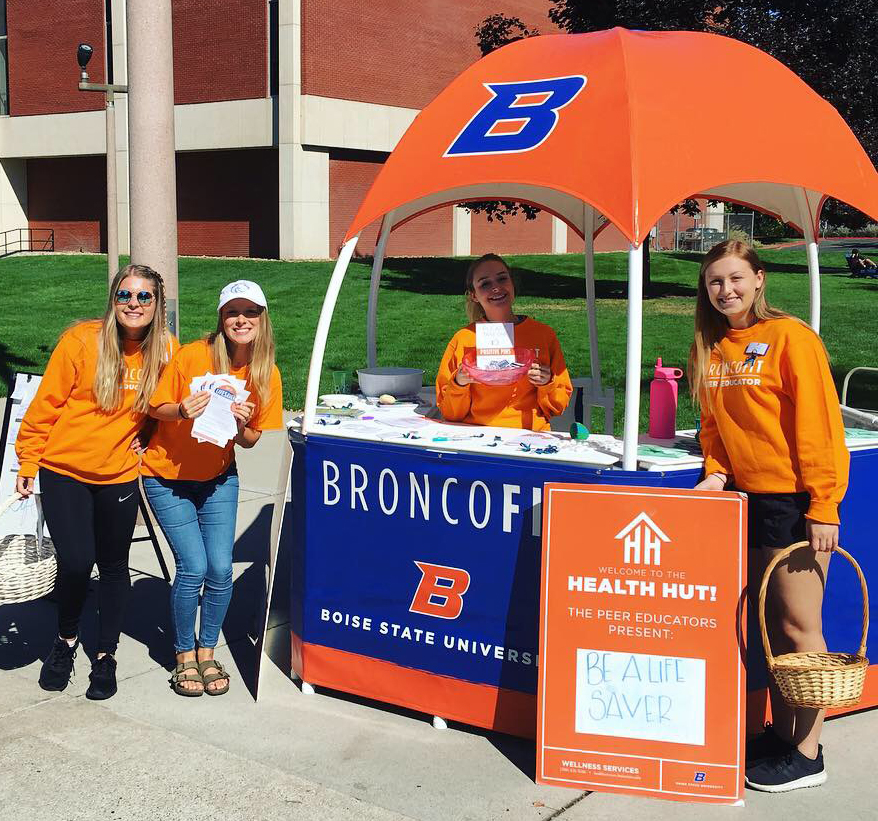 Peer Educators handing out goodies at their tent on the Boise State Quad