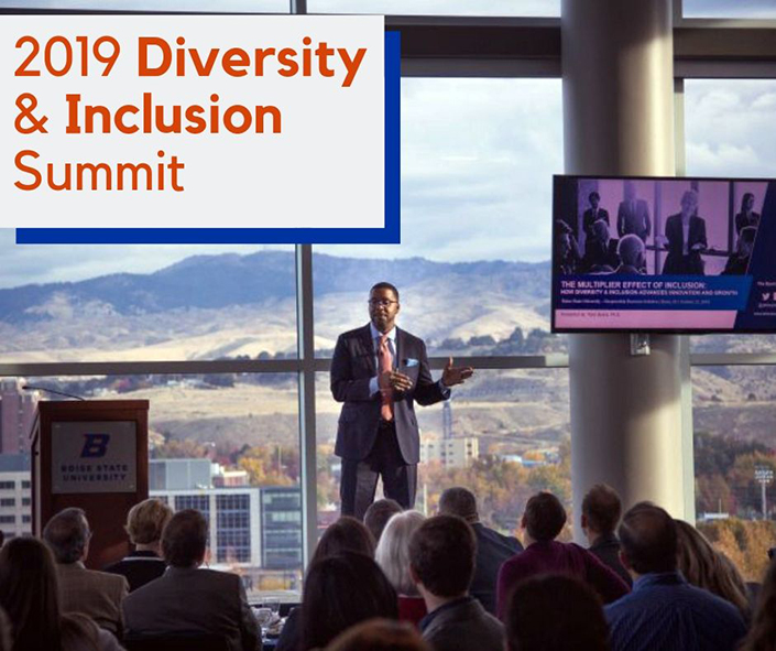 """Picture of speaker and sign that reads """"2019 Diversity & Inclusion Summit"""""""