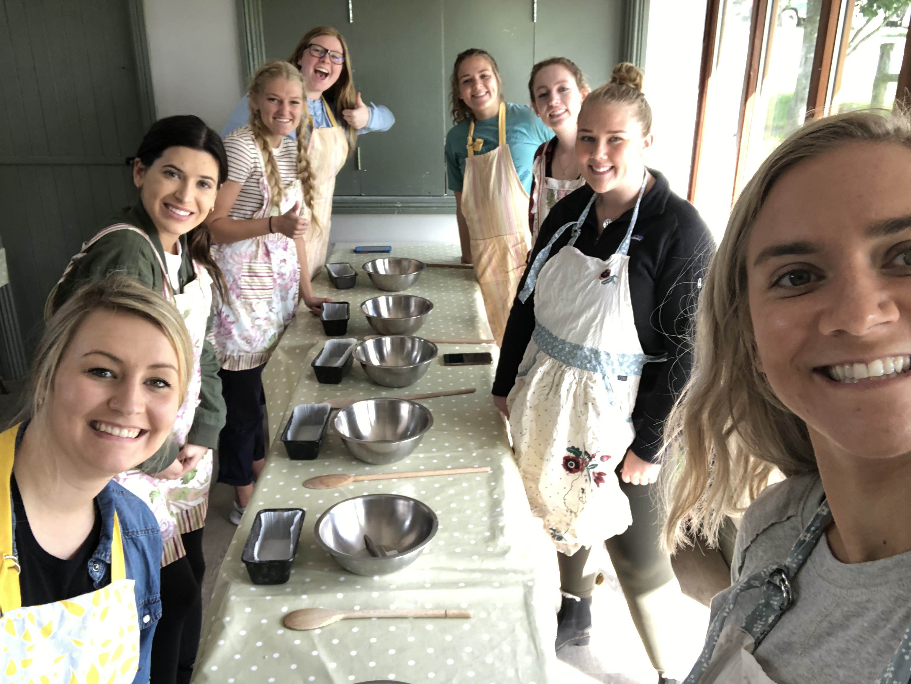 Students posing next to a table while they learn how to make bread