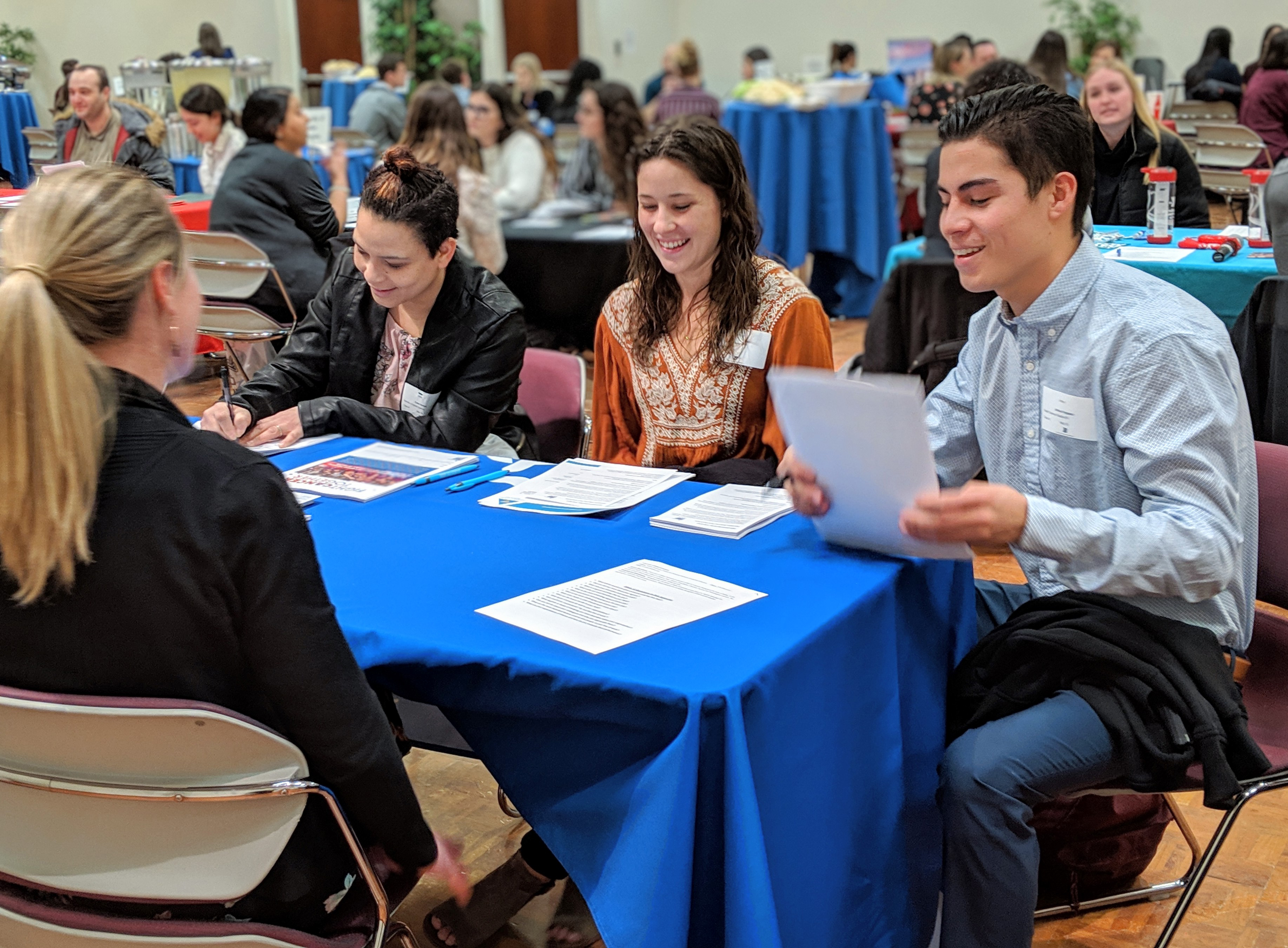 Student handing employer a resume at the meet and greet