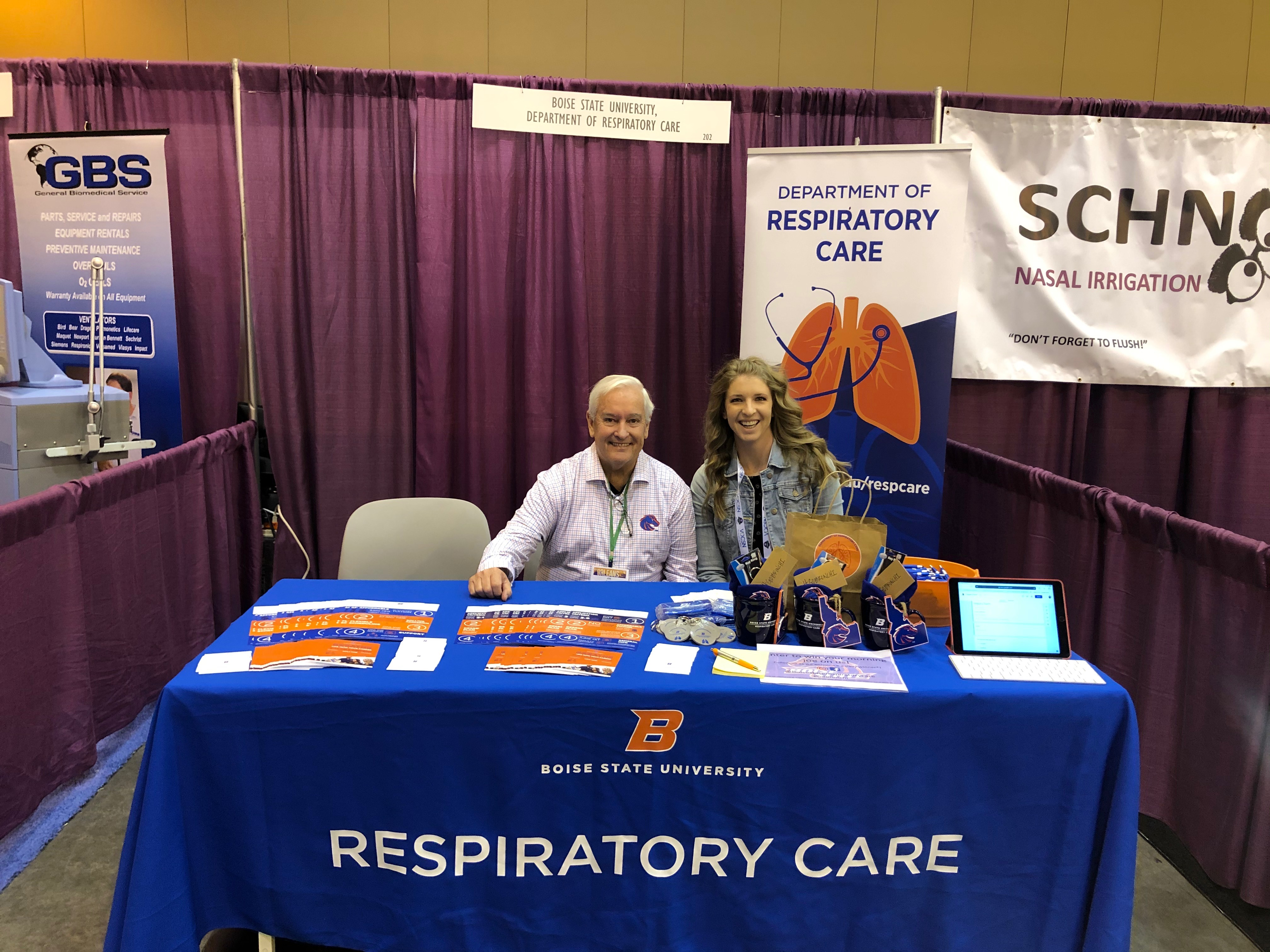 """Faculty sitting at a table at the event that reads """"Respiratory Care"""""""