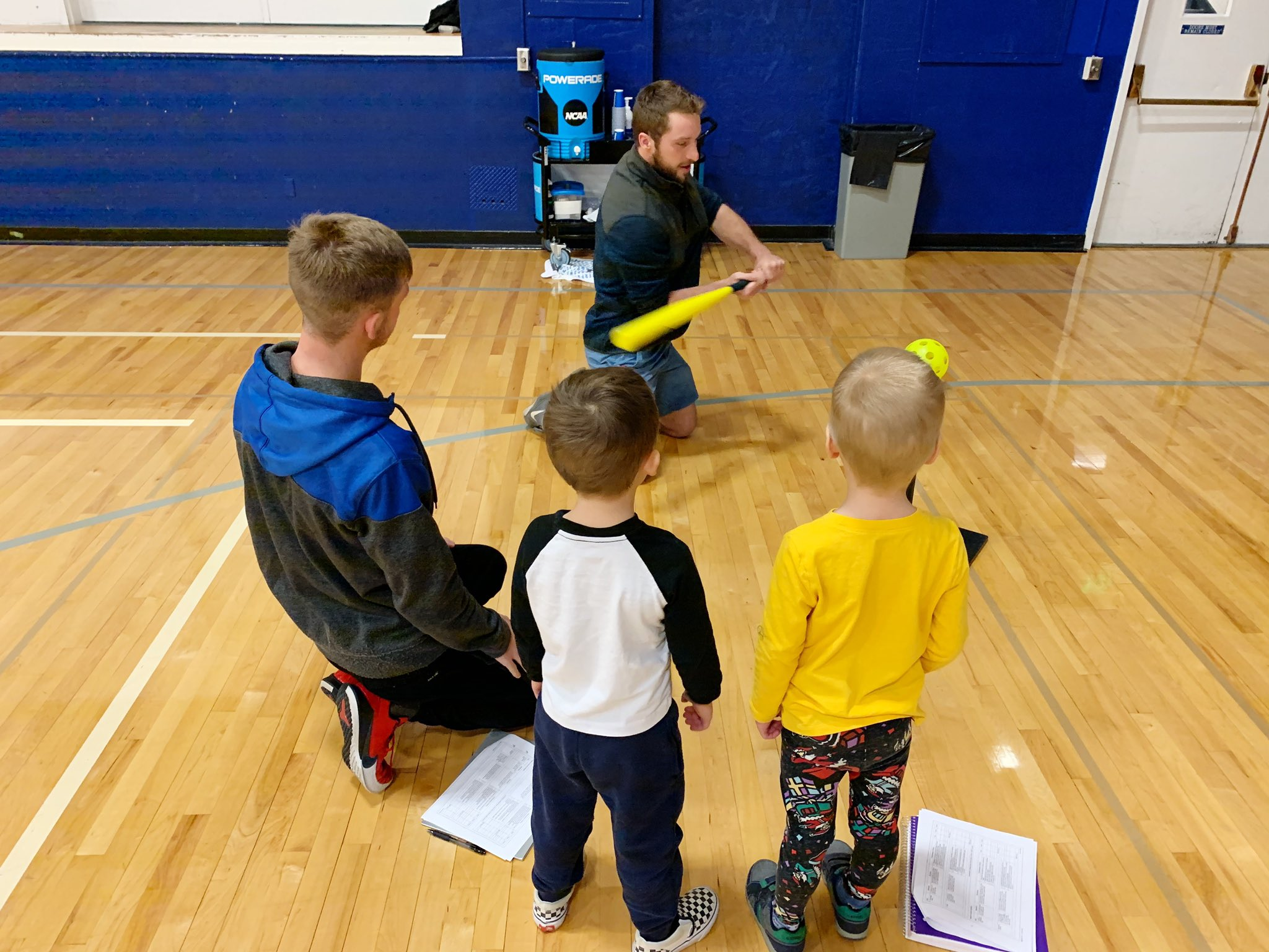 Kines student teaching kids how to hit a ball with a bat