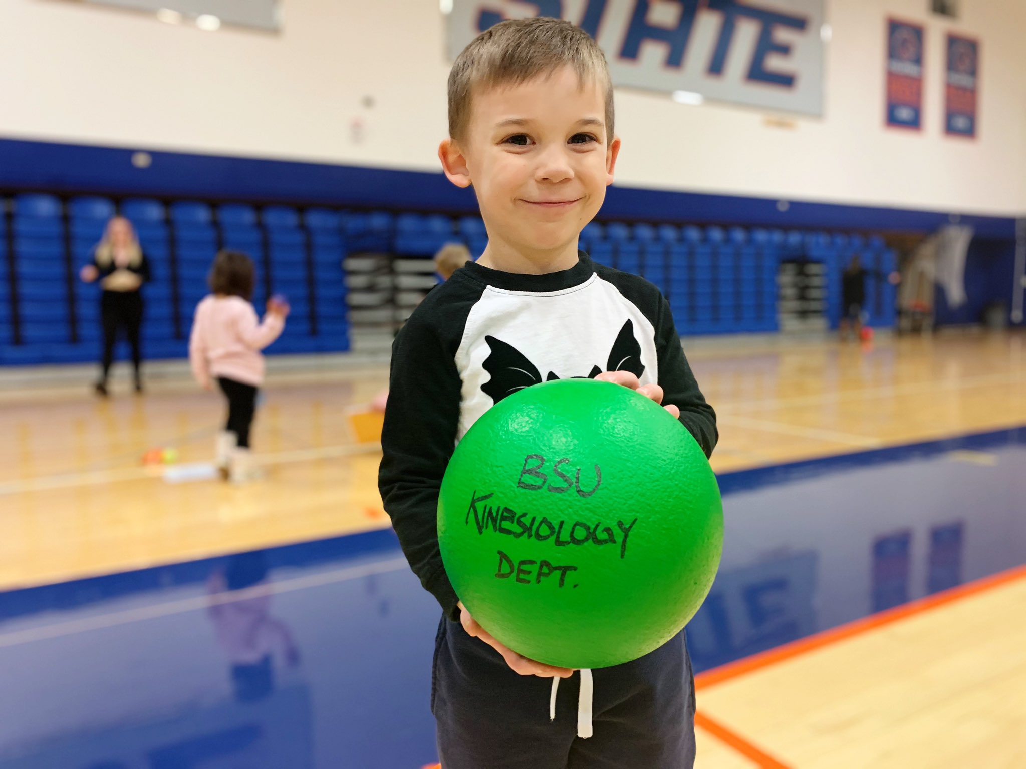 Young child holding a ball in a gym