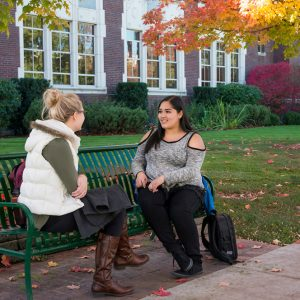 Two students sit on a bench on Boise State University's campus