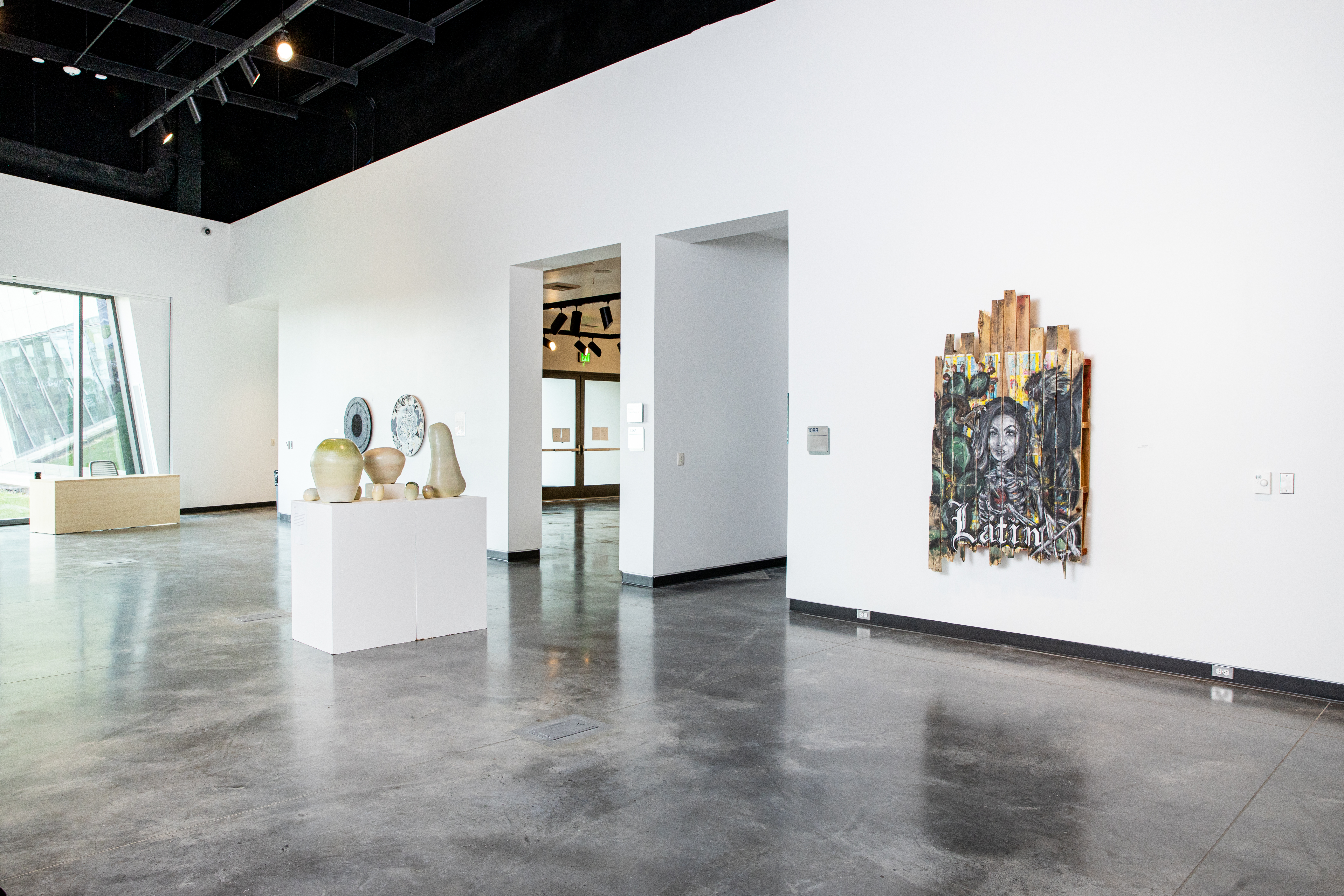 Blue Galleries space with art displayed on walls and pedestals.