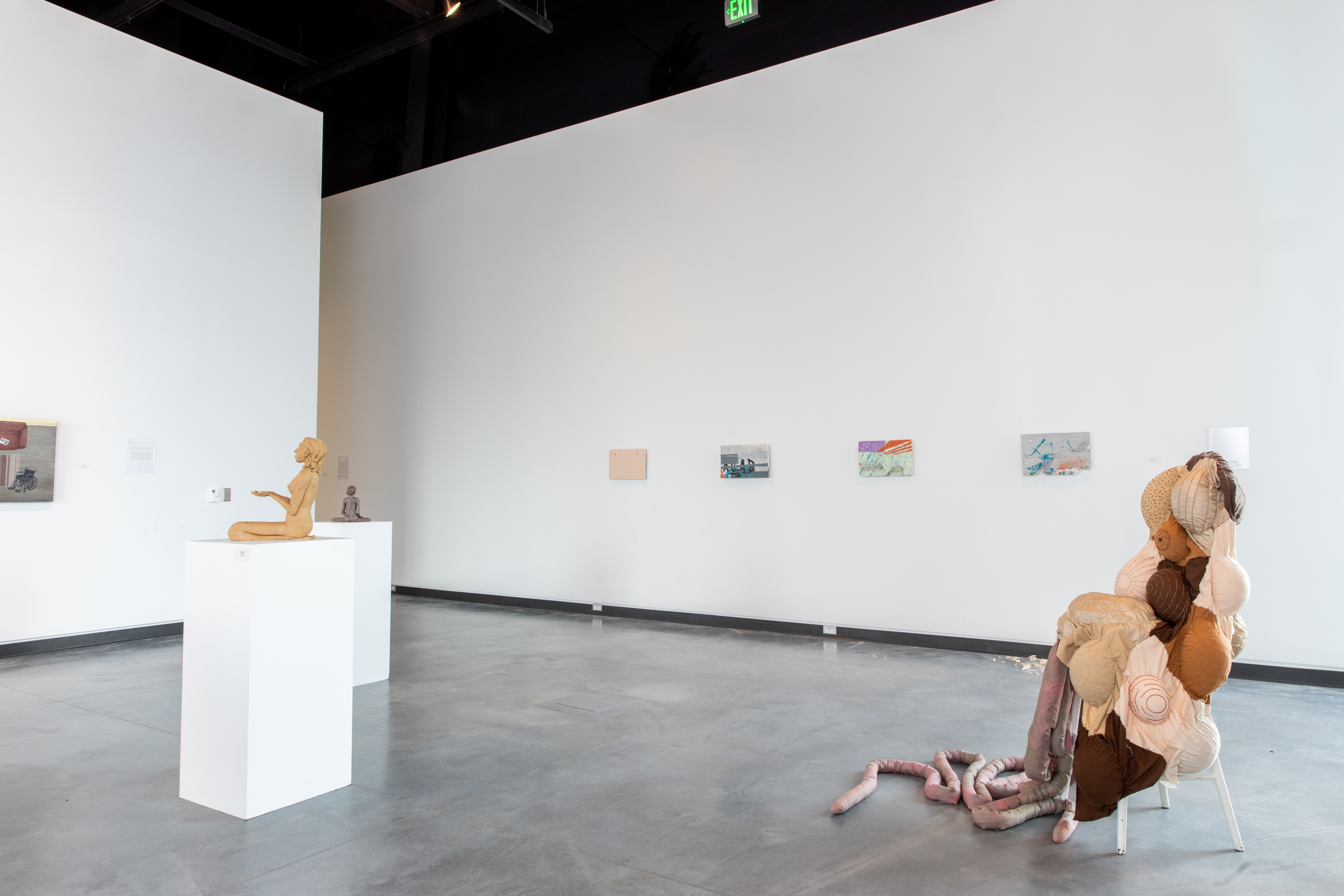 Blue Galleries space with art displayed on walls, pedestals and a large floor piece.
