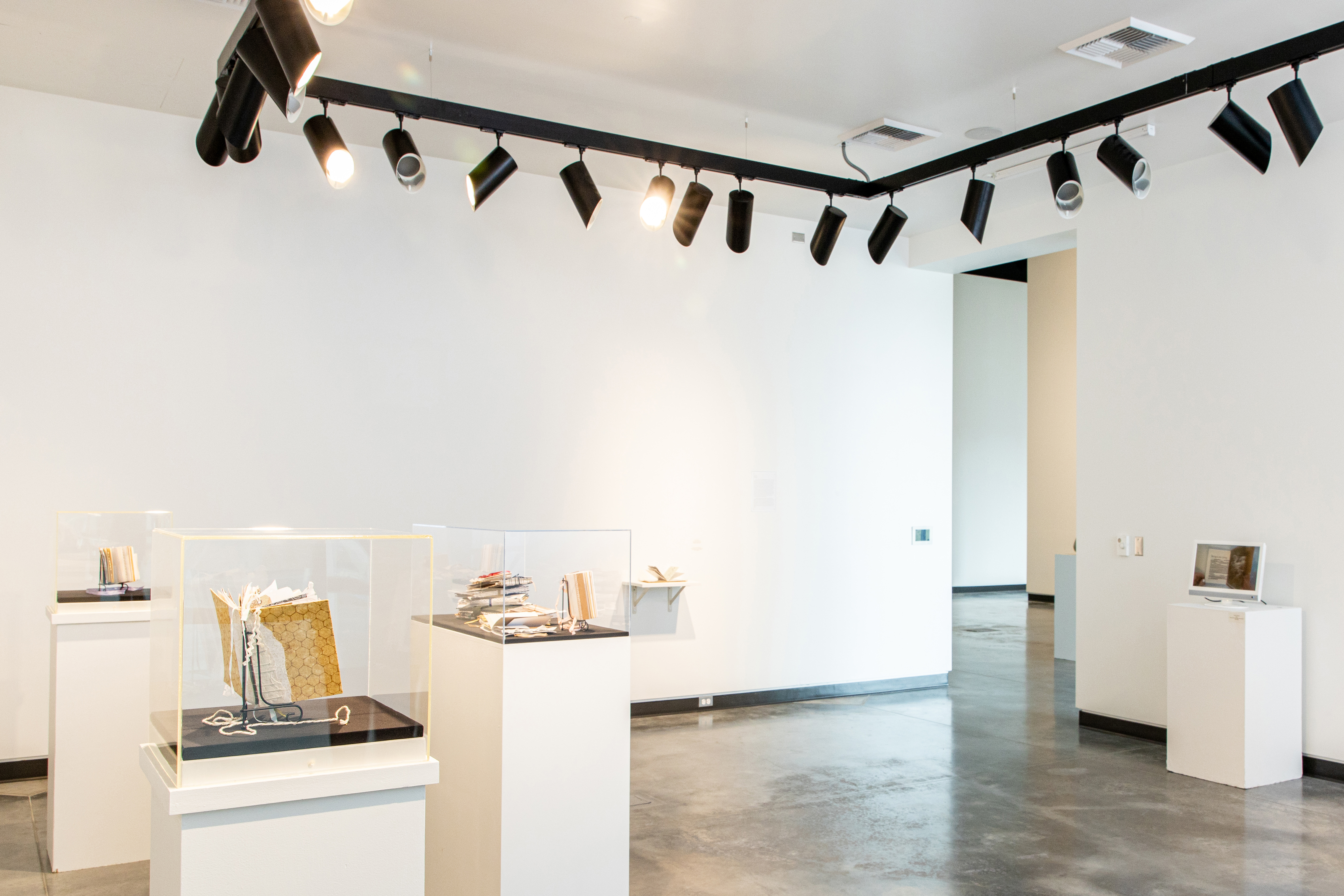Student gallery space with art displayed on white pedestals.