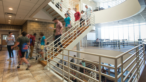 Students walking in a hall and on a staircase