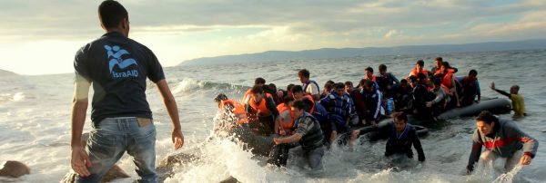 Photo of refugees arriving by boat on a beach