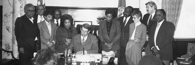 historical photo of Marilyn Shuler with Governor Evans signing a bill