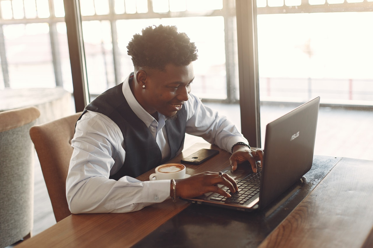 positive-young-businessman-working-on-laptop