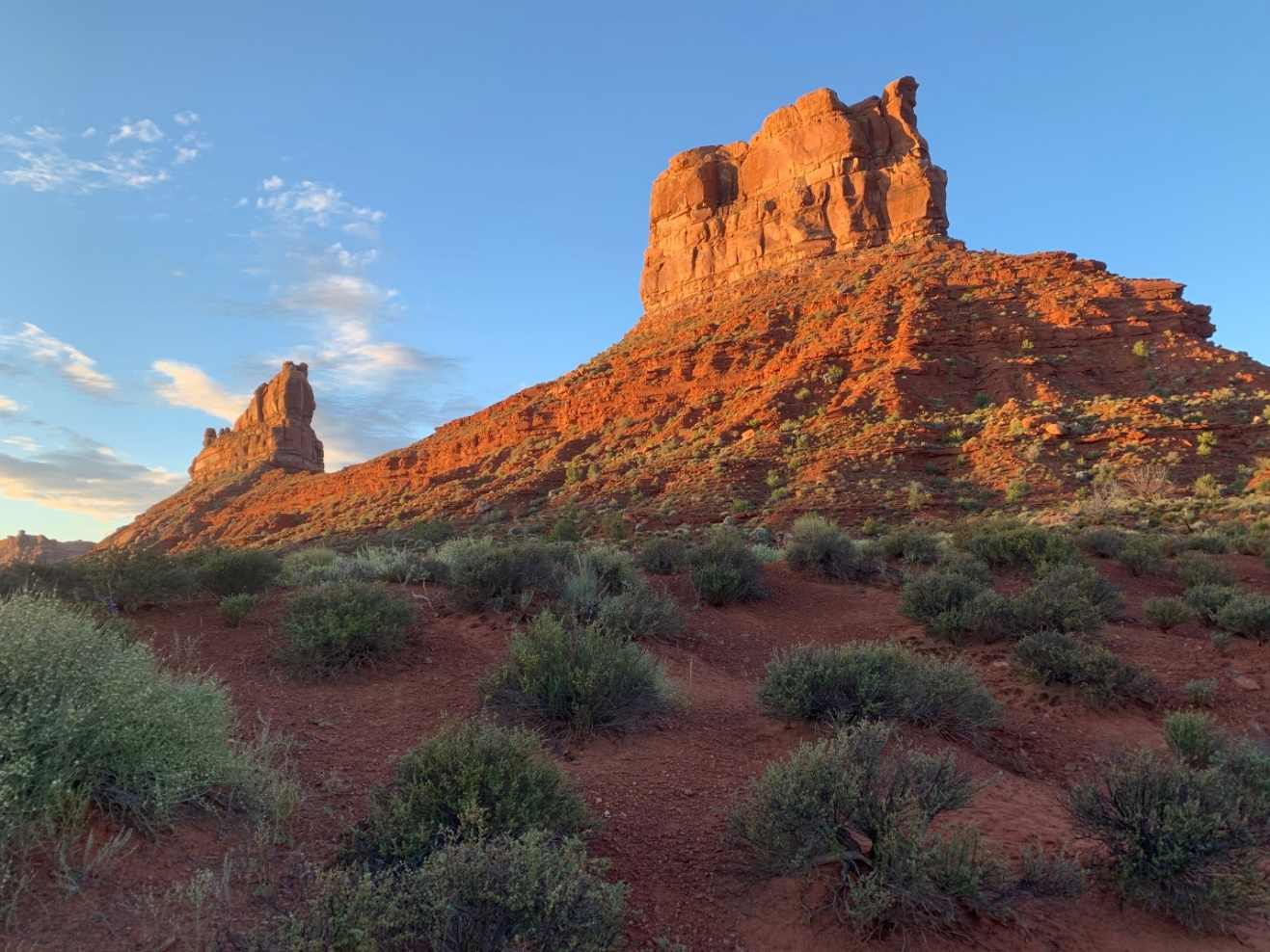 a huge red rock tower sticks up on the horizon with a characteristic utah view