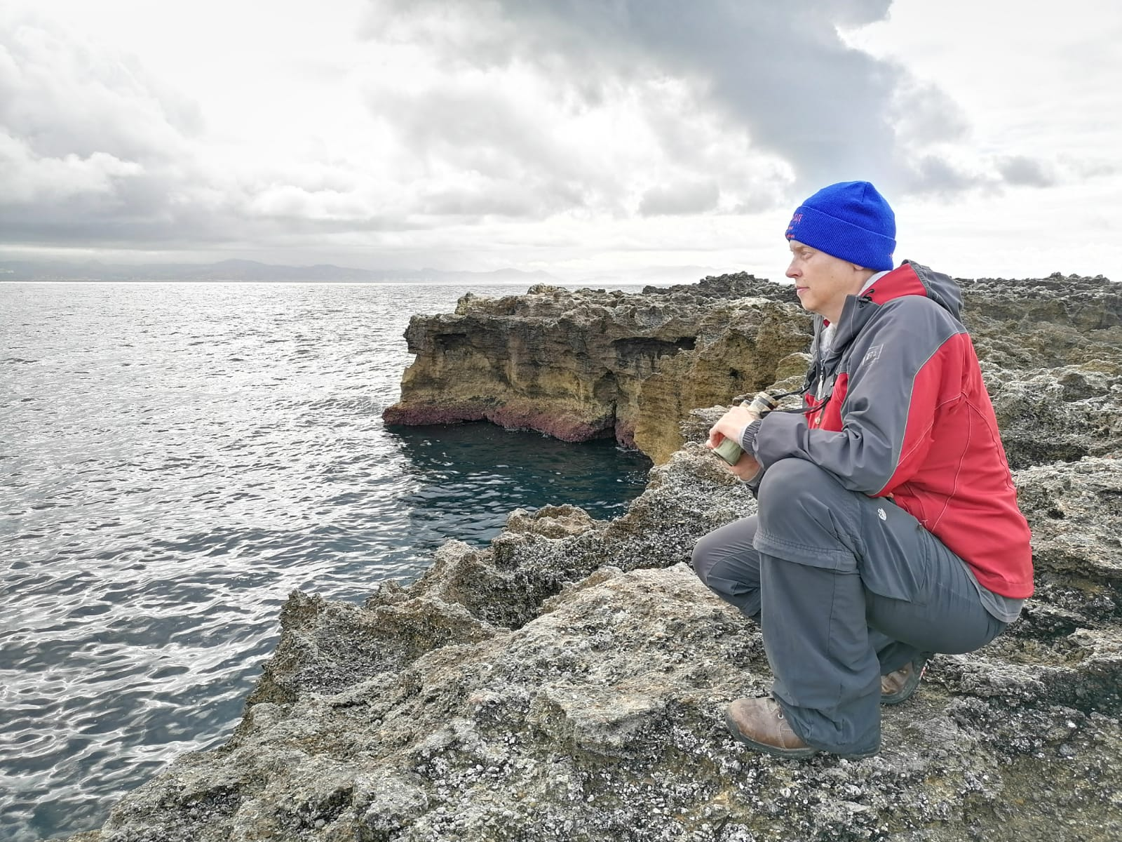 a scientist in a boise state hat kneels on a cliff edge overlooking the ocean, holding binoculars