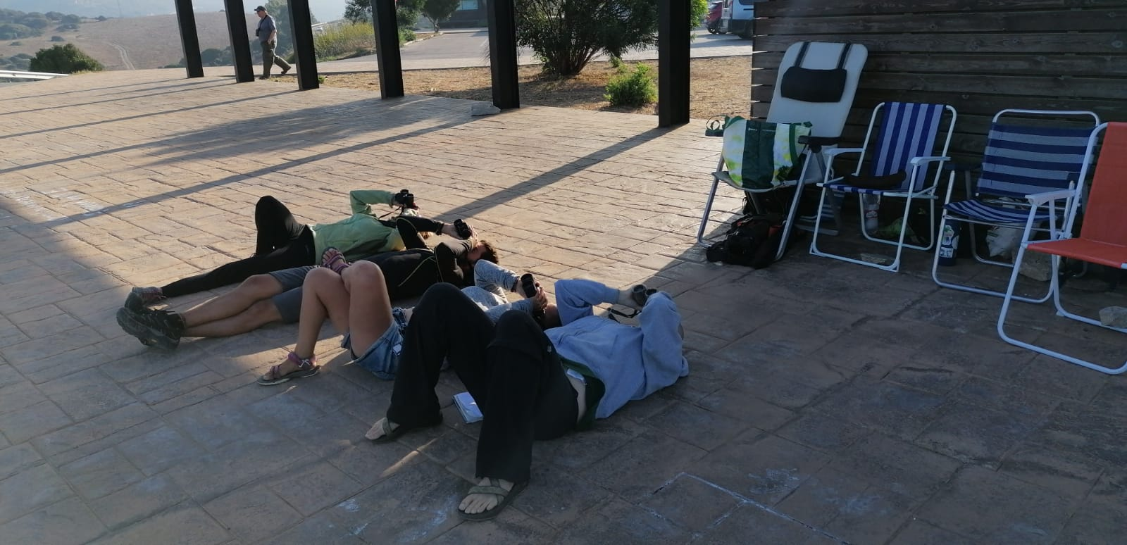 three scientists lay flat on their backs with binoculars pointed into the sky overhead