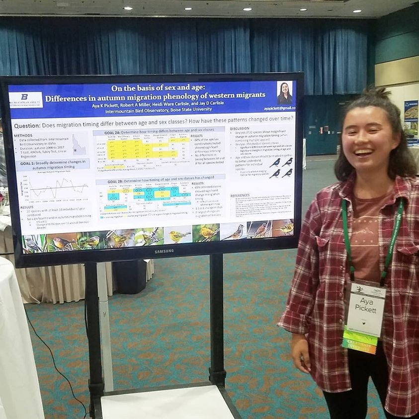 a female undergraduate student stands smiling next to her research poster which displays a number of graphs and small text