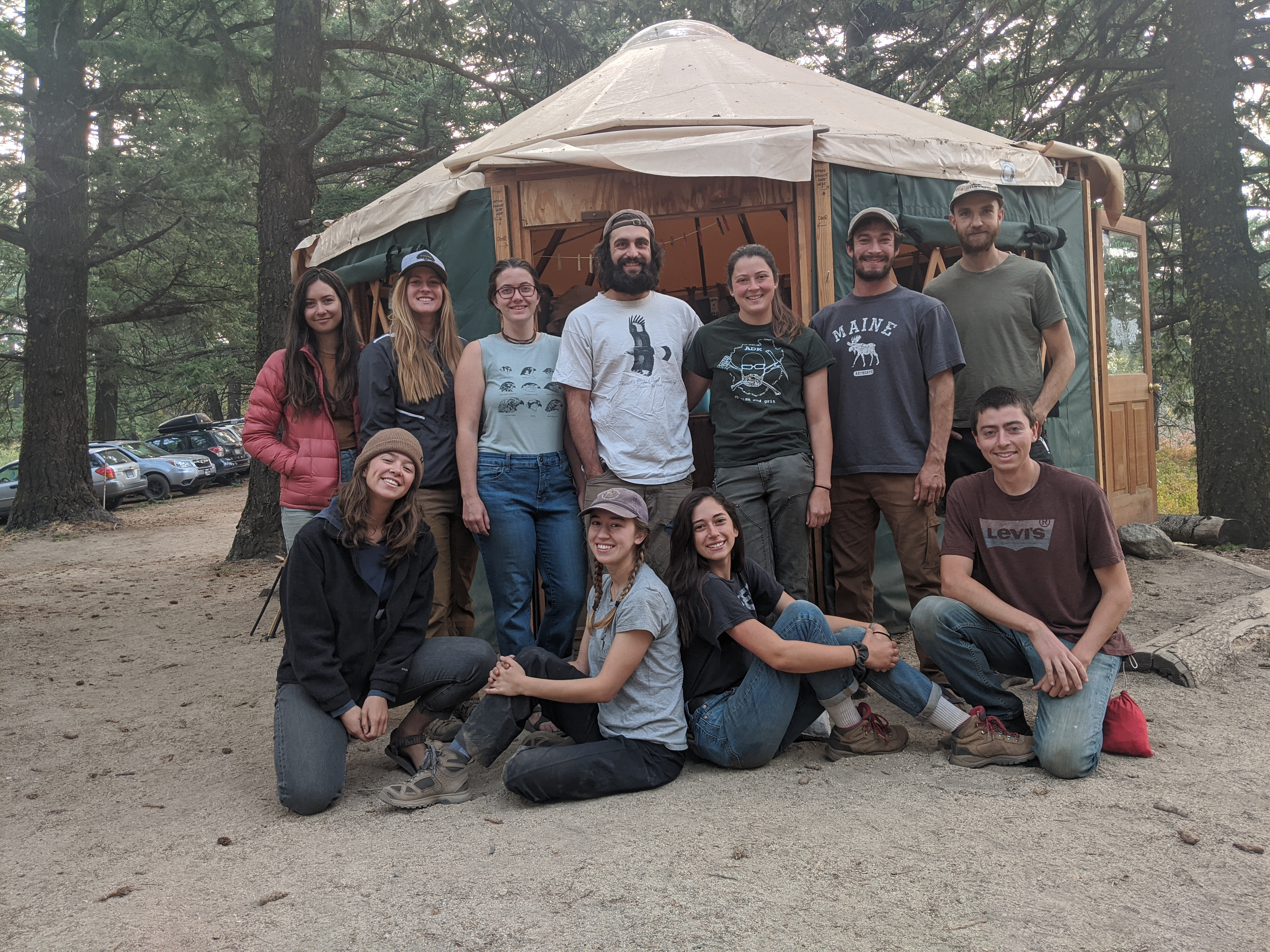 a group of young biologists stand in the forest in front of a yurt
