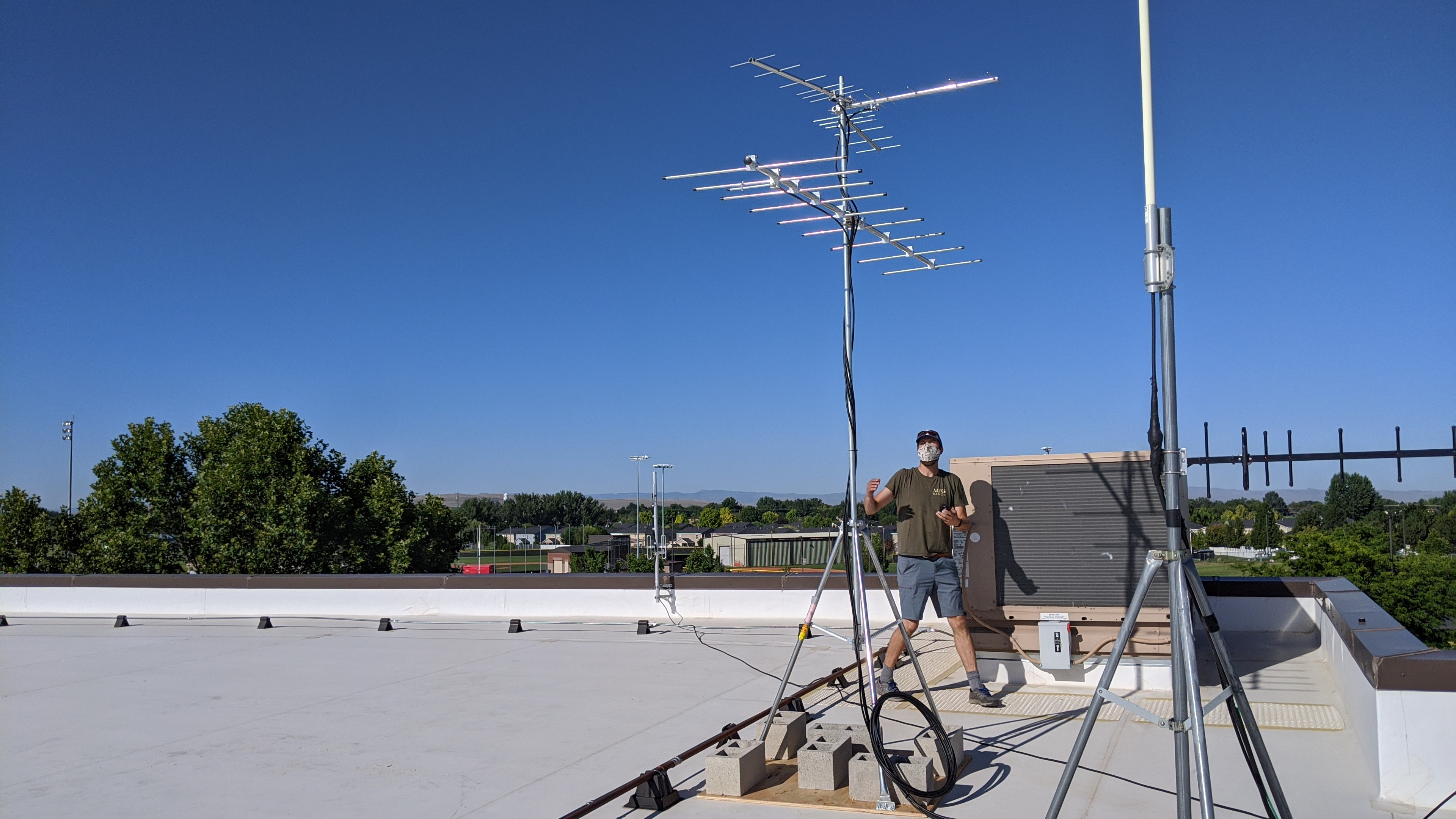 a biologist wearing a cloth face mask stands on the flat roof of a building looking up at an antenna array and unfurling a wire attached to the antenna