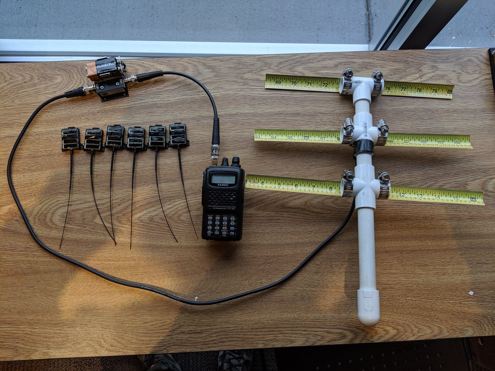 six small transmitters with antennas sit on a desk with a larger t-shaped receiver antenna