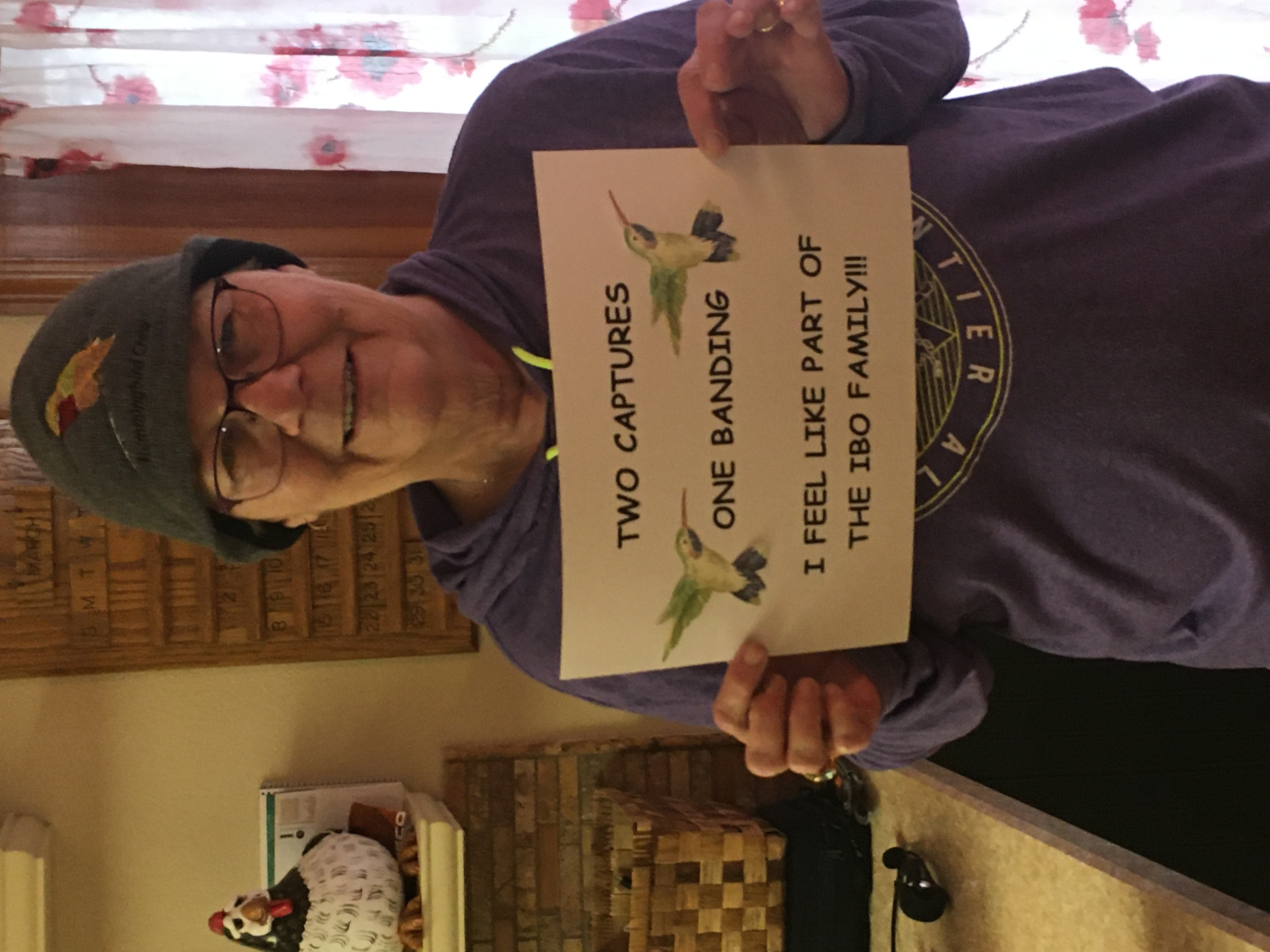 """a woman with thinning hair wears a warm knit hat with a hummingbird embroidered on it. she's holding a sign with hummingbird clipart on it that reads """"two captures one banding. I feel like part of the IBO family!!!"""""""