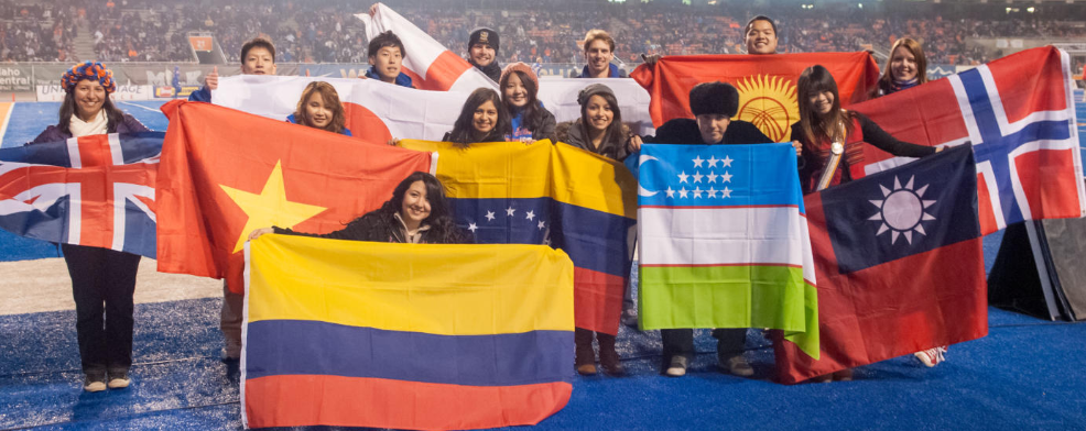 International students proudly displaying their country's flags on the blue turf