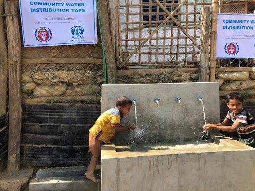Two children drinking from a fountain in a Rohingya camp