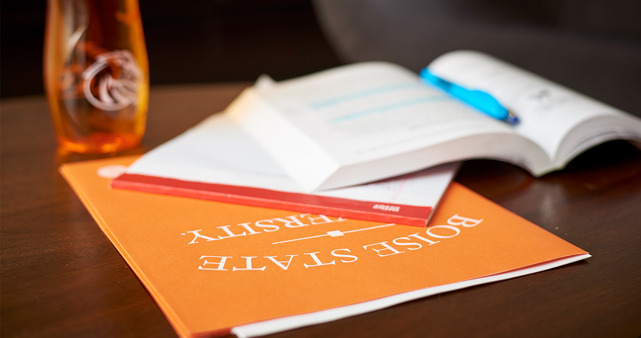 Student success materials like water bottles, folders and textbooks sit on a tabletop