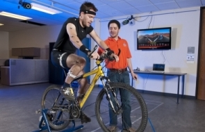 Researcher working with subject, tracking movements on a bike