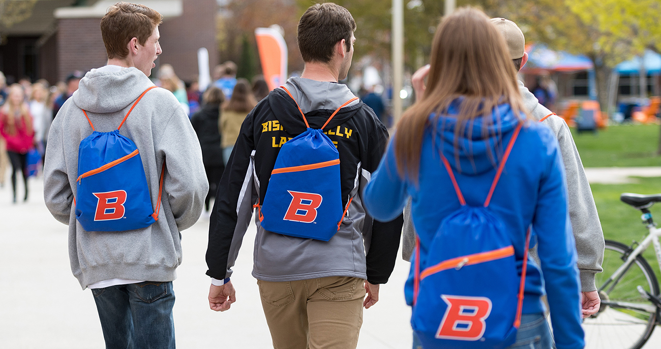Students walking down path with Boise State backpacks