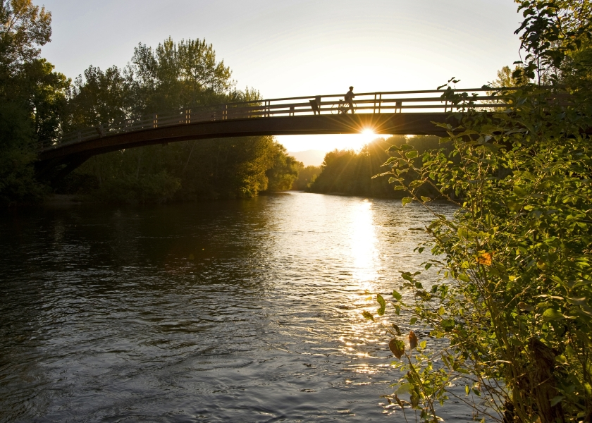 a person crossing Boise state friendship bridge with river and a setting sun