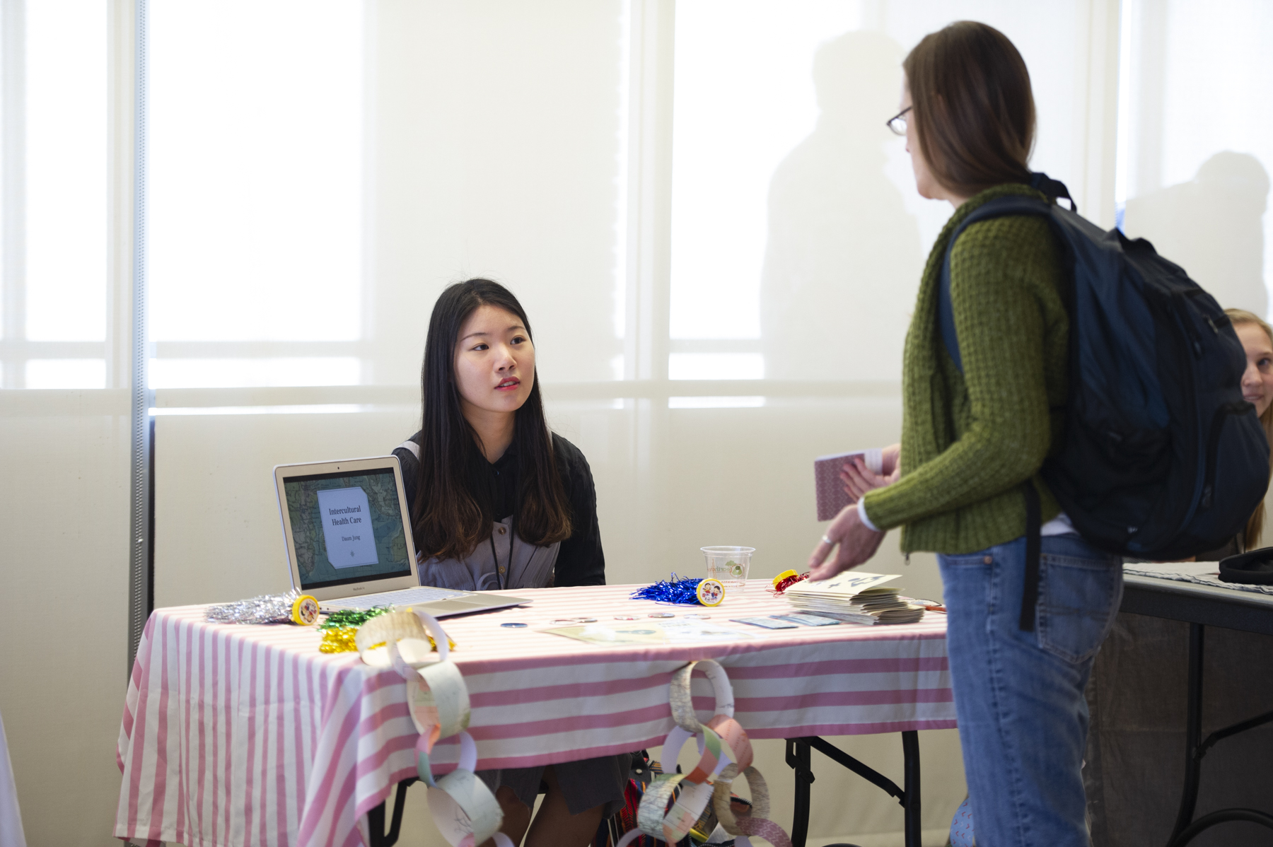 One student presenting their work to an attendee