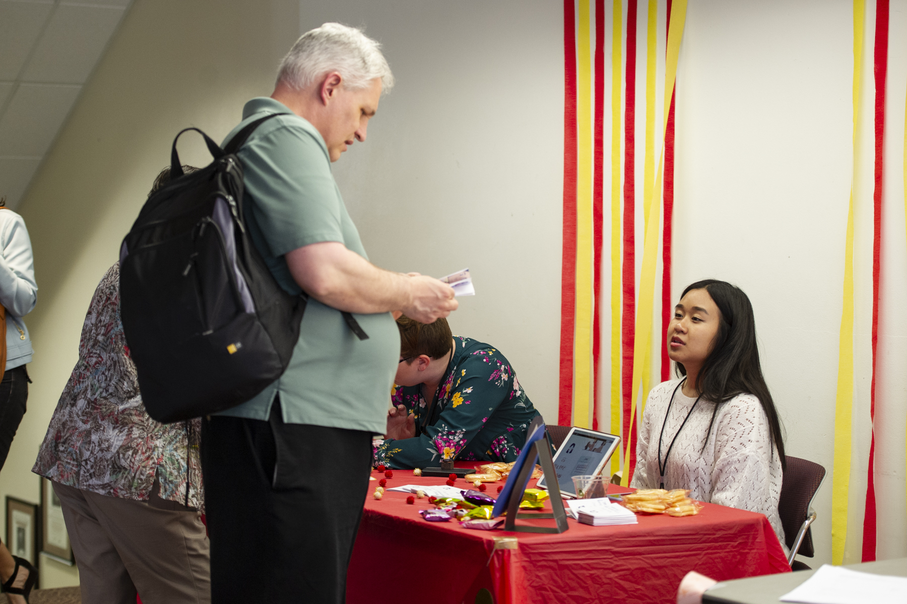 Teacher talking to a student at a booth displaying curriculum for K-12 students.