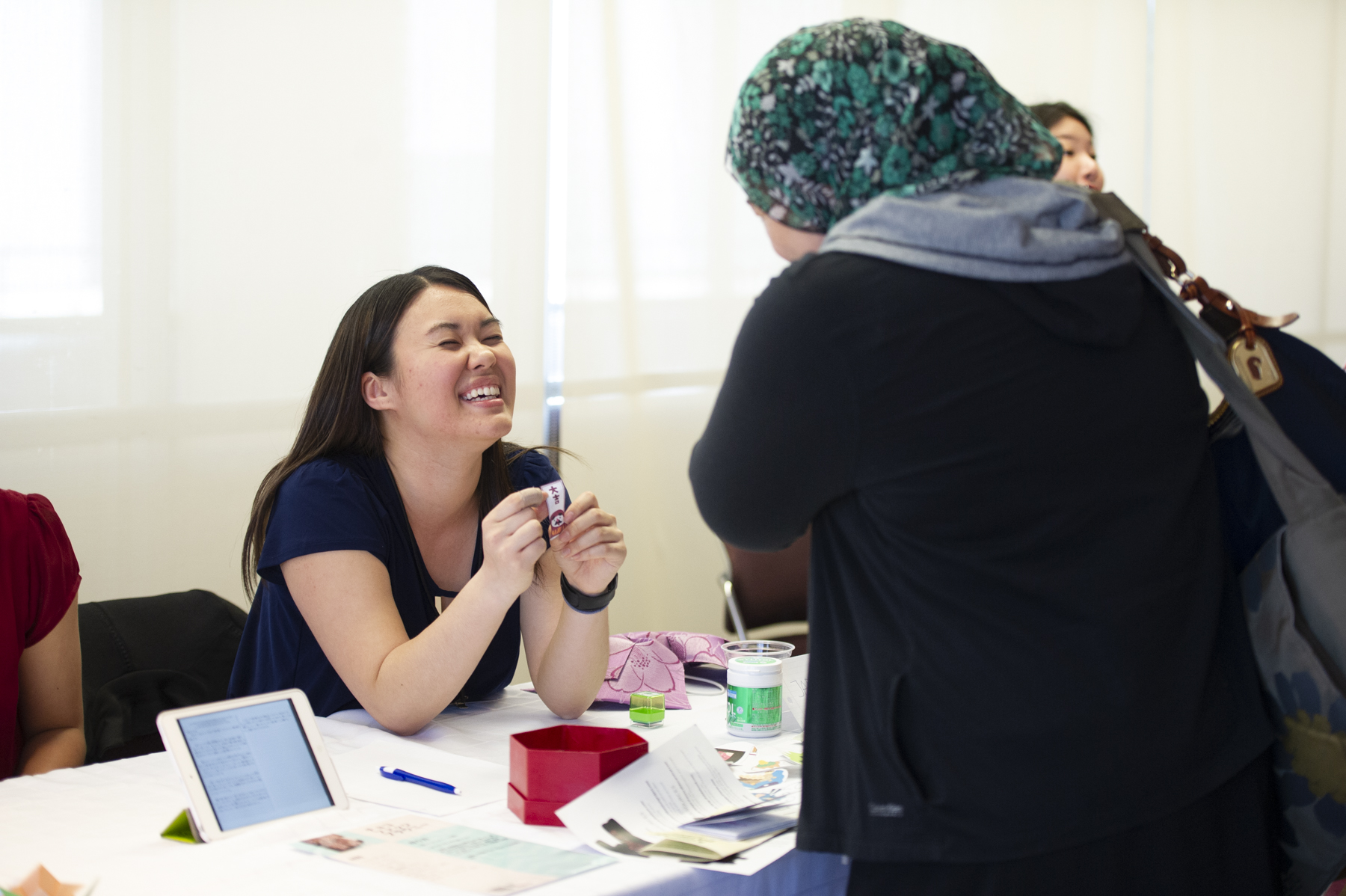 Student laughing, speaking with an attendee