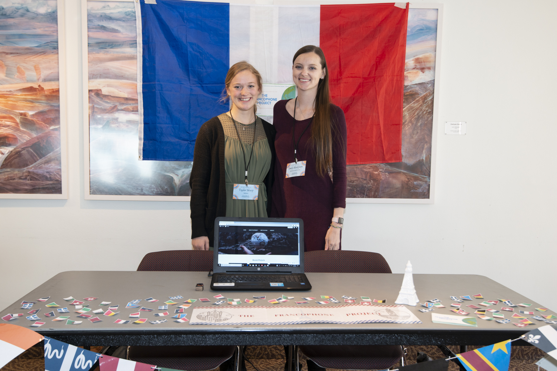 2 Students smiling with their table setup