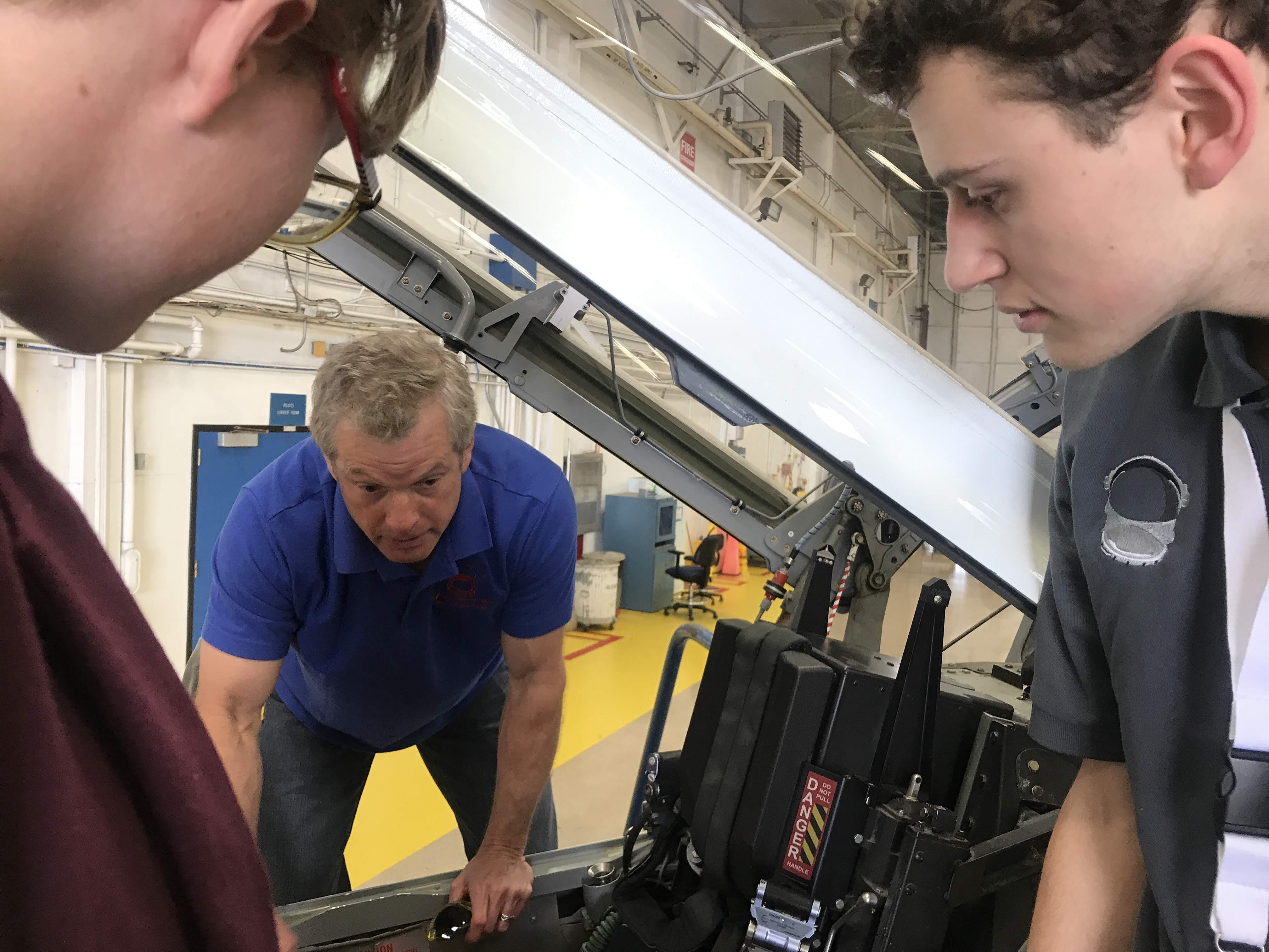 Dr. Steve Swanson and VIP students examining spacecraft