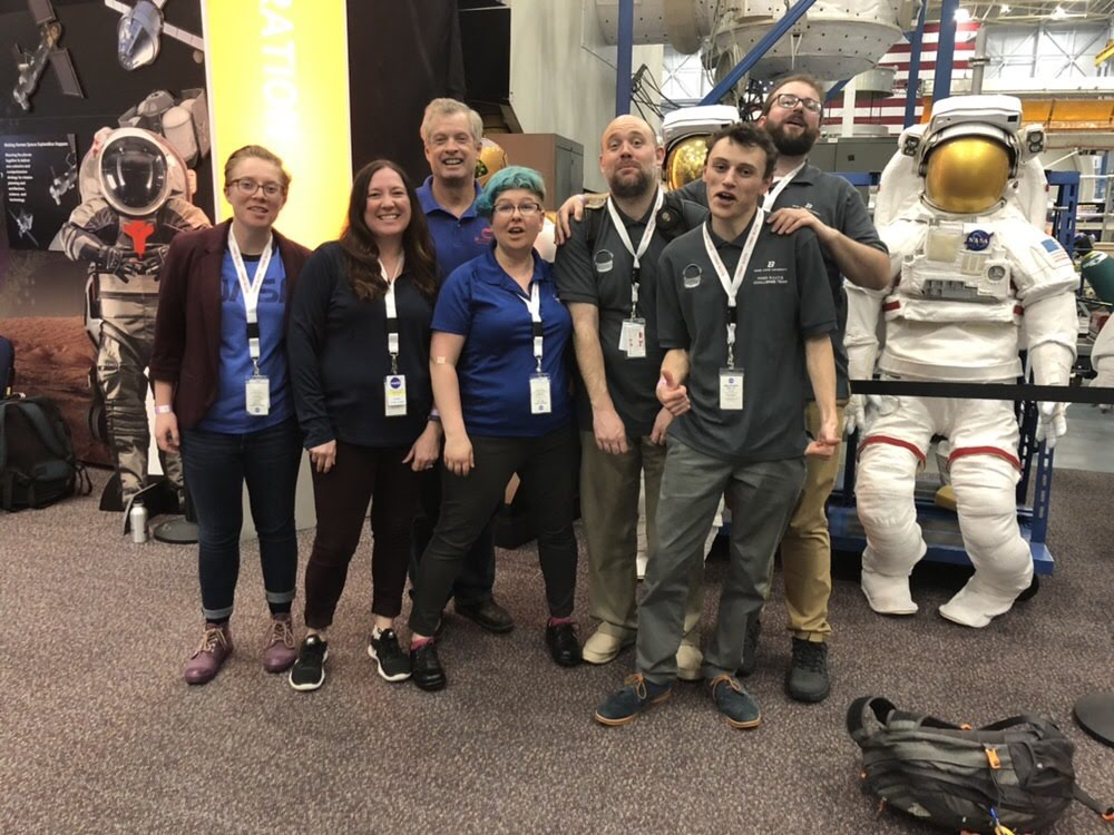 NASA Team inside Johnson Space Center, smiling in front of the camera