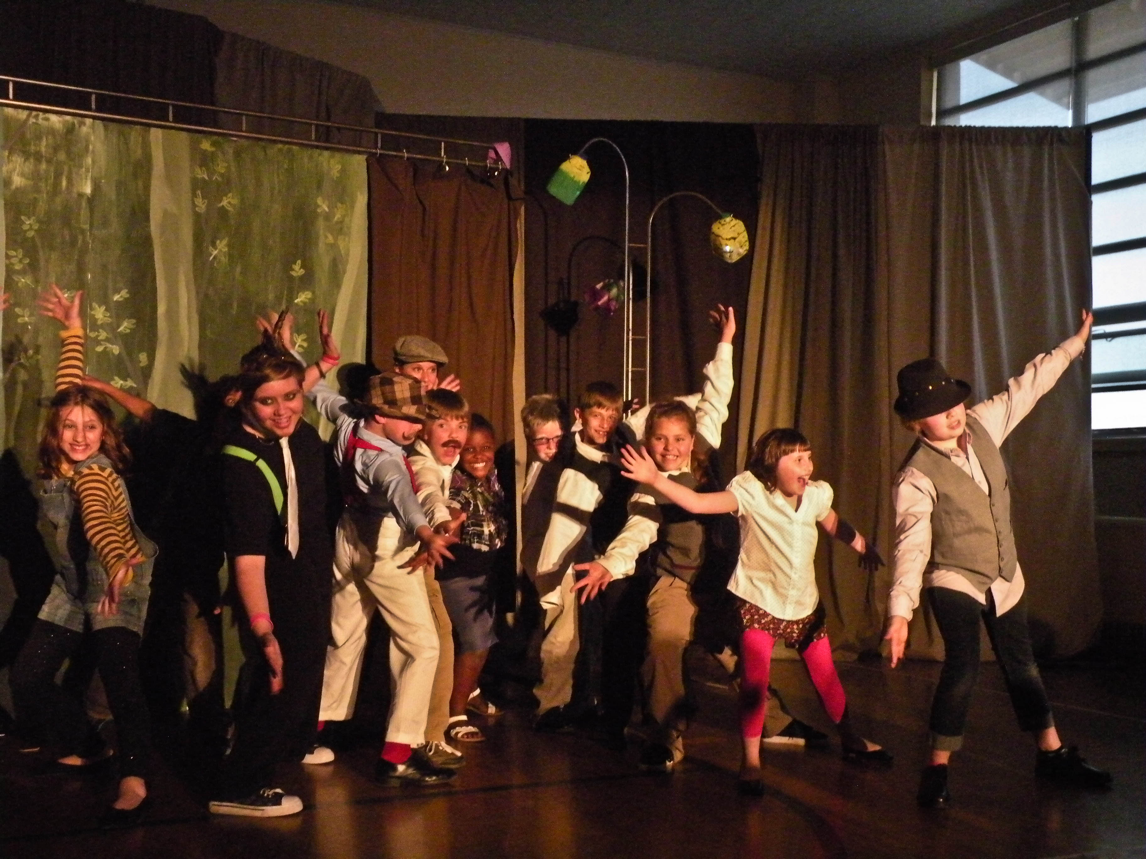 Group of 15 kids in full costume doing jazz hands