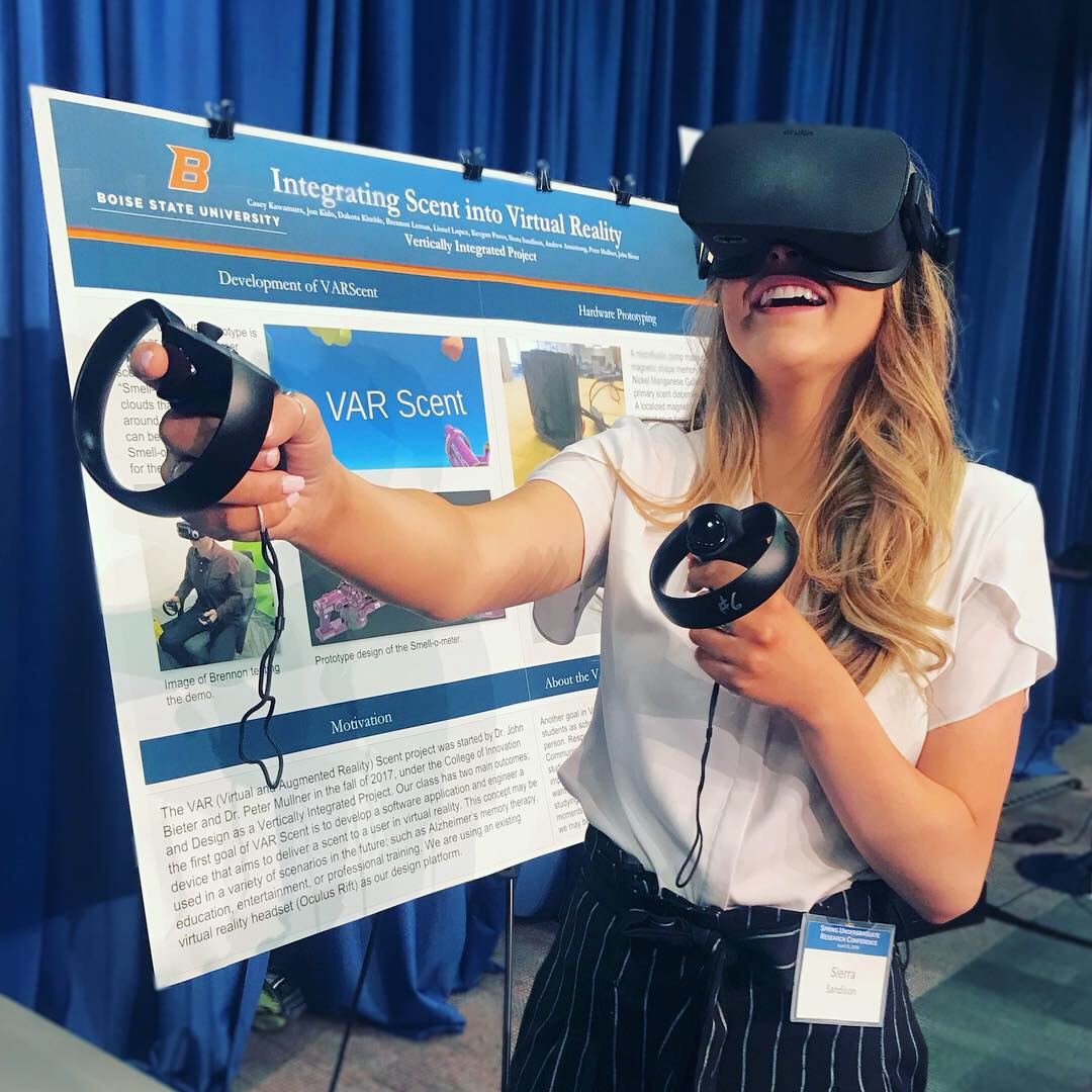 Student stands in front of academic poster at a poster conference. She is wearing a VR headset and is using hand controls.
