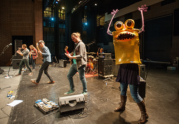 """Photo of local band Lakoda playing on stage in the Special Events Center while Treefort """"monsters"""" dance alongside the band."""