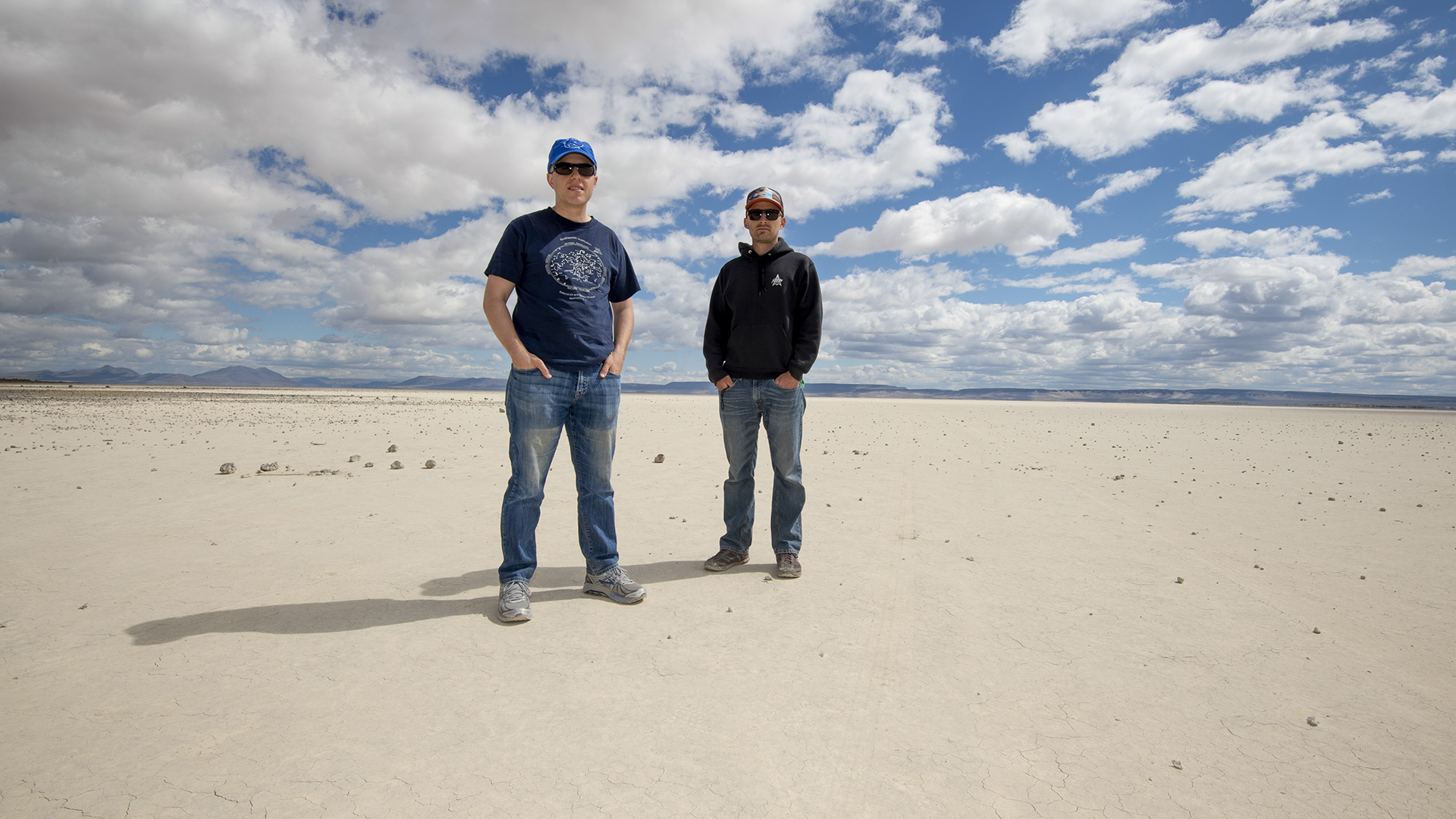 Two people standing in a wide, flat desert