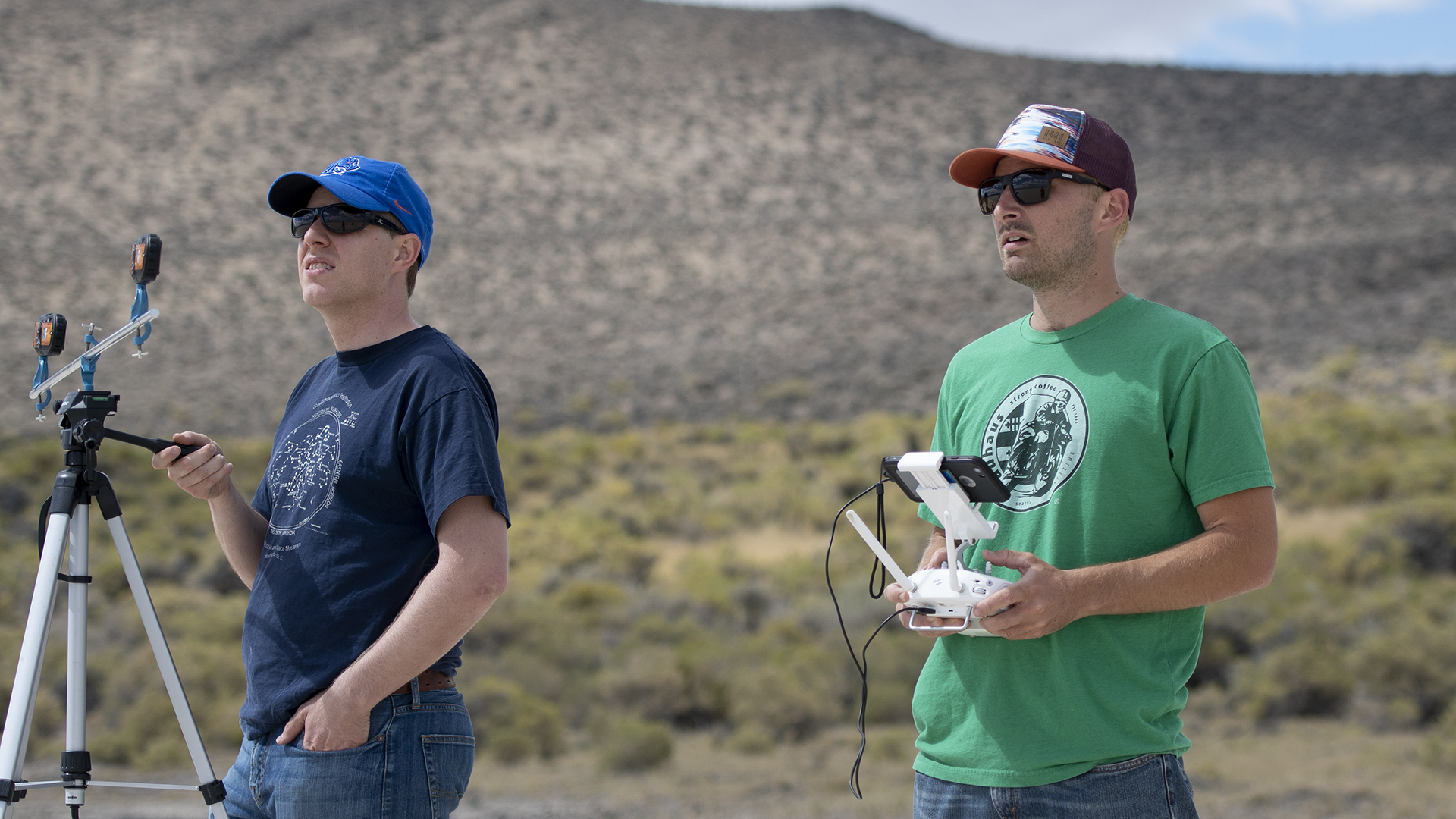 One researcher holding onto tripod, the other one piloting the drone with a controller