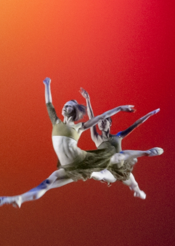 Dancers leaping through air on stage