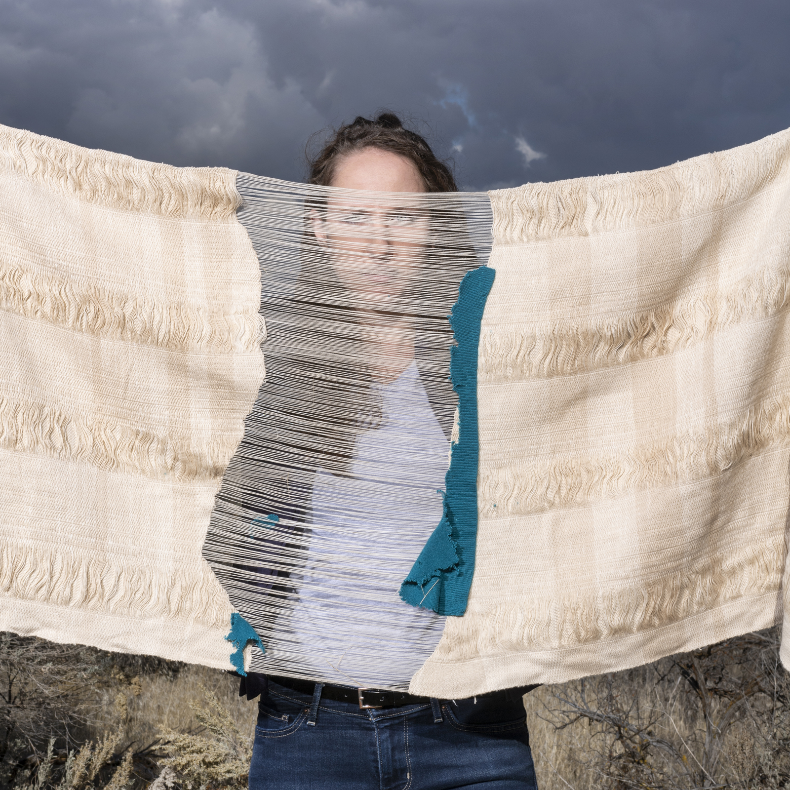 Artist Lily Lee holding burial shroud in front of her face
