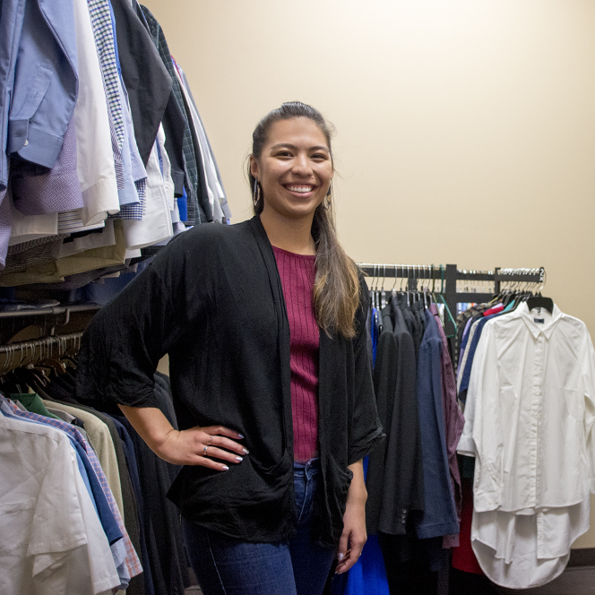 A woman poses in a closet