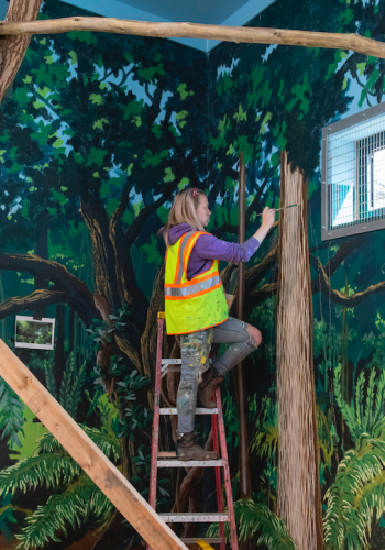 A student paints a wooded scene at Zoo Boise