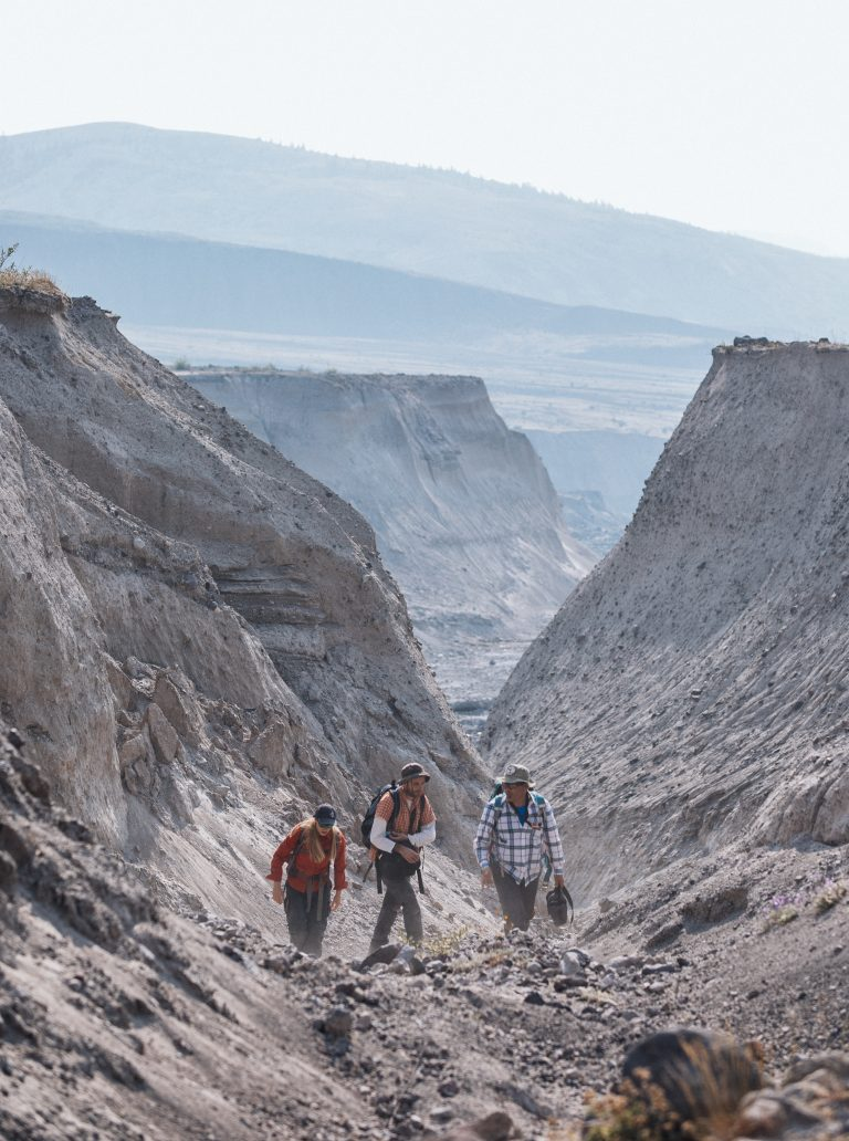 Three students walking in canyon